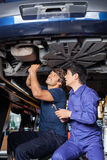 Mechanics Working Underneath Lifted Car Stock Photography