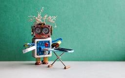 Mechaniczny prasowanie usługa pojęcie Domowego robota sprzątania prasowania czerni pomocniczy cajgi z żelazem na desce Zieleń Obrazy Stock