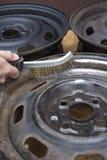 Mechanik czyści stalowego koło obręcz ręcznie z drucianym muśnięciem zdjęcia stock