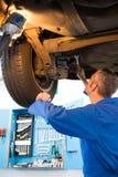 Mechanik egzamininuje pod samochodem zdjęcia royalty free
