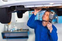 Mechanik egzamininuje pod samochodem z pochodnią fotografia stock