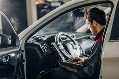 Mechanik Egzamininuje Samochodowego silnika Z pomocą laptop obrazy royalty free