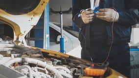 Mechanik elektryczny w samochodowym garażu warsztacie pracuje z voltmeter - elektryczny drutowanie zdjęcie stock