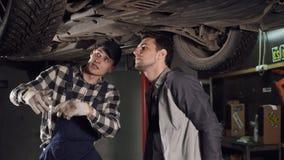 Mechanik i jego męski klient sprawdza out naprawiającego veicle Klient trząść ręki z auto remontową usługa zbiory