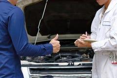 Mechanik i klient między naprawianie silnikiem samochód przy samochód usługa garażem obraz stock