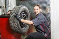 Mechanik kobieta pracuje na samochodzie w jego sklepie Zdjęcia Royalty Free
