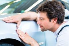 Mechanik kontroluje lakę w samochodowym warsztacie obrazy stock