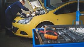 Mechanik naprawia samochód garażuje usługa - odśrubowywa szczegół samochód - obraz stock