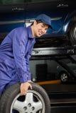 Mechanik Niesie Samochodową oponę Przy Auto Remontowym sklepem Fotografia Royalty Free