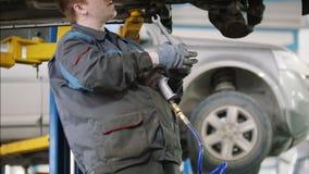 Mechanik odśrubowywa szczegół samochód w kapiszonie - samochodu usługowy naprawianie, zakończenie up zbiory