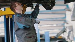Mechanik odśrubowywa szczegół samochód w kapiszonie - samochodu usługowy naprawianie, zakończenie up zdjęcie wideo