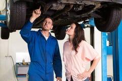 Mechanik pokazuje klientowi problem z samochodem Zdjęcia Stock