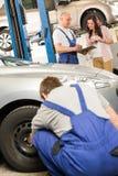 Mechanik pokazuje papierkową robotę właściciel samochodu zdjęcia royalty free