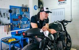 Mechanik pozuje z motocyklem zdjęcia royalty free