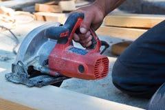 Mechanik pracuje na budowie z kółkowym saw, Drewniany przerób obrazy stock