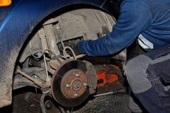 Mechanik pracuje na jego kolanach na zmielonym naprawianiu starego samochód zdjęcie stock