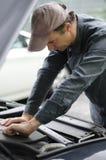 Mechanik pracuje na samochodu silniku z kapiszonem otwartym obraz royalty free