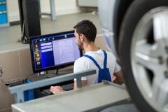 Mechanik pracuje na samochodzie komputerem Obrazy Royalty Free