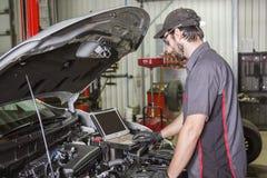 Mechanik pracuje na samochodzie w jego sklepie obrazy stock