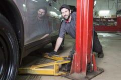 Mechanik pracuje na samochodzie w jego sklepie obraz royalty free