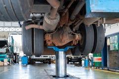 Mechanik pracuje z tylni axle redukcyjną przekładnią ciężarowy utrzymania stacja obsługi zdjęcia stock