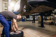 Mechanik przystosowywa opony koło przy remontowym garażem zdjęcie royalty free