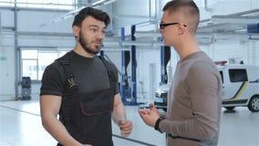 Mechanik rozdaje z klientem o samochodowym naprawianiu zdjęcie wideo