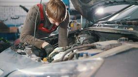 Mechanik sprawdza automobilowego silnika i naprawia, samochód naprawa, pracuje w warsztacie pod kapiszonem, przegląd, zdjęcie wideo