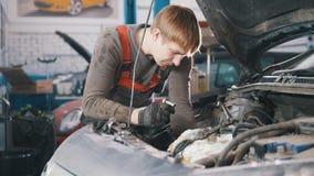 Mechanik sprawdza automobilowego silnika i naprawia, samochód naprawa, pracuje w warsztacie pod kapiszonem, przegląd, obraz stock