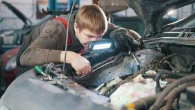 Mechanik sprawdza automobilowego silnika i naprawia, samochód naprawa, pracuje w warsztacie pod kapiszonem, przegląd, zbiory wideo