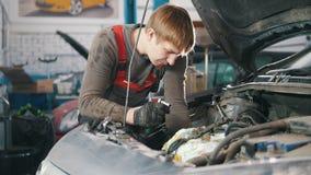 Mechanik sprawdza automobilowego silnika i naprawia, samochód naprawa, pracuje w warsztacie, przegląd zdjęcie wideo