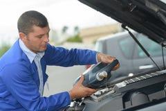 Mechanik sprawdza nafcianego poziom w samochodowym warsztacie zdjęcie royalty free
