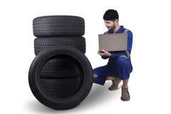 Mechanik sprawdza opony z laptopem zdjęcie stock