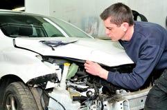 Mechanik sprawdza samochodowego ciała szkodę przy auto remontowego sklepu usługa Zdjęcia Stock