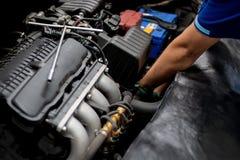 Mechanik sprawdza samochodowego silnika w auto naprawie obrazy stock