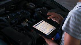 Mechanik sprawdza silnika w auto remontowym sklepie używać cyfrową pastylkę zbiory wideo