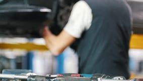 Mechanik stawia śrubokręt na stole w samochodowym remontowym sklepie zbiory