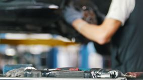 Mechanik stawia narzędzia na stole w samochodowym remontowym sklepie zbiory wideo