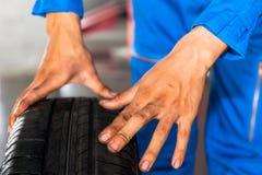 Mechanik trzyma i sprawdza samochodowy toczy wewnątrz samochodowej garaż usługa fotografia stock