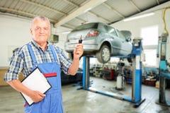 Mechanik trzyma samochodowego kluczowego atauto remontowego sklep   zdjęcia royalty free