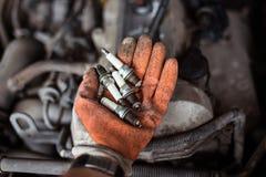 Mechanik trzyma stare łamać samochodowe iskrowe prymki obrazy stock