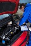 Mechanik używa laptop podczas gdy naprawiający samochód zdjęcia royalty free