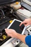 Mechanik używa pastylkę załatwiać samochód zdjęcie royalty free
