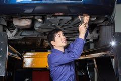 Mechanik Używa wyrwanie Pod Podnoszącym samochodem obrazy stock