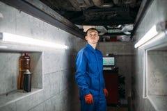Mechanik w jama czeków dnie samochód fotografia stock