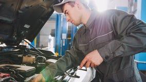Mechanik w kombinezonów czekach równych parowozowy olej w samochodzie - samochodu usługowy naprawianie obrazy stock