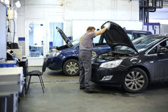 Mechanik w kombinezon otwierającym kapiszonie czarny samochód Obrazy Stock