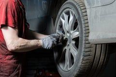 Mechanik w usługowym centrum sprawdza zawieszenie brudny samochód Wykonuje sezonowego koła zastępstwo obrazy royalty free