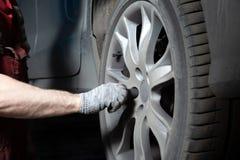 Mechanik w usługowym centrum sprawdza zawieszenie brudny samochód Wykonuje sezonowego koła zastępstwo zdjęcie stock