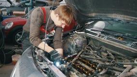 Mechanik z lampą naprawia automobilowego silnika, samochód naprawa, pracuje w warsztacie zbiory